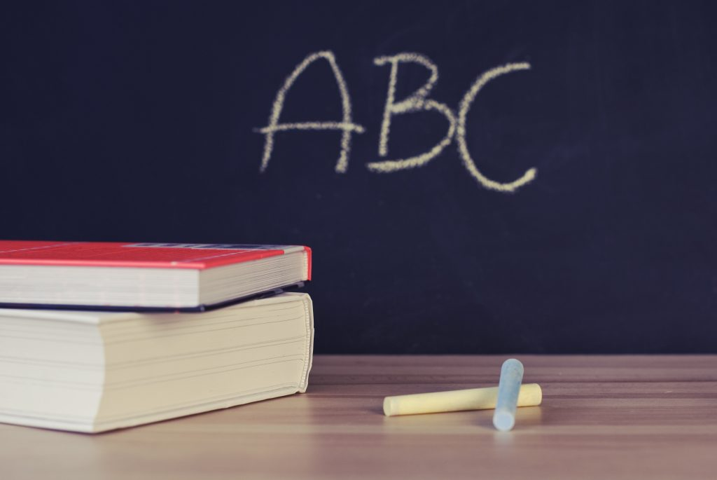 Photo of two textbooks and two pieces of chalk sitting on a table top. In the background are the letters ABC written in chalk on a blackboard.