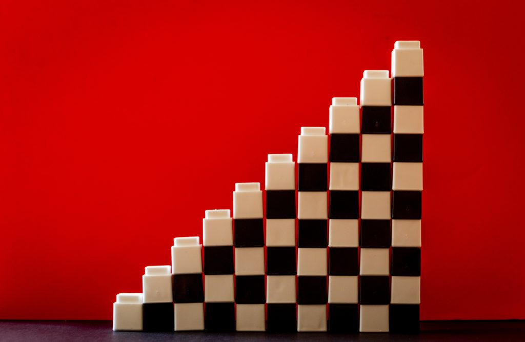 A stack of alternating black and white blocks in front of a red background